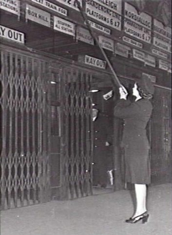 Australian War Memorial image #126587 - Miss Peace Harber, one of the first women railway employees, changing the indicator clocks at the Degraves Street entrance of Flinders Street Station.