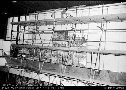 Hanging the first pieces of the mural in the great hall at Spencer Street Station 18-6-1974 (PROV image VPRS 12800/P1, item H 4219)